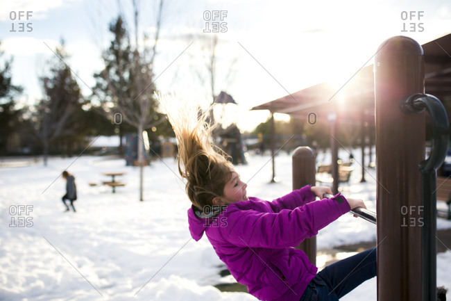 Girl playing on wooden structure at park during winter