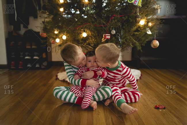 Brothers kissing sister while sitting against Christmas tree at home