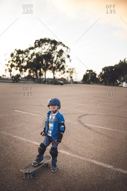 Portrait of cute boy standing with skateboard at field against clear sky