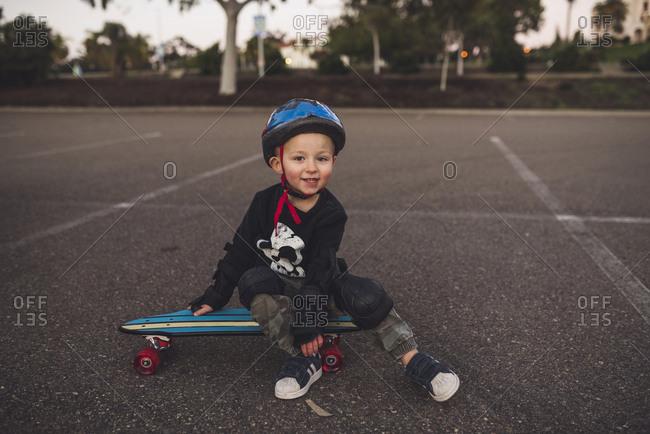 Portrait of cute boy sitting on skateboard at field