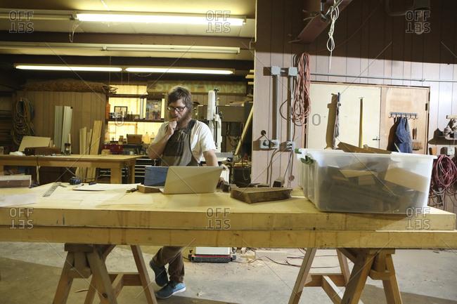 Confident carpenter working in workshop