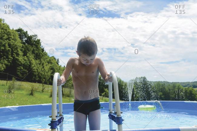 Shirtless boy holding railing while standing in wading pool