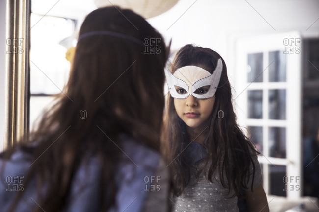 Girl wearing eye mask looking in mirror at home