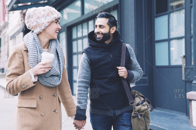 Happy couple holding hands while walking on footpath in city
