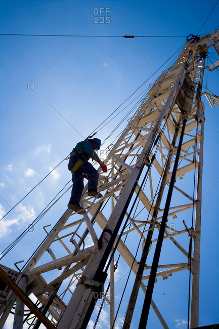Low angle view of man climbing on crane against blue sky