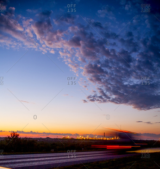 Light trails on road against cloudy sky during sunset
