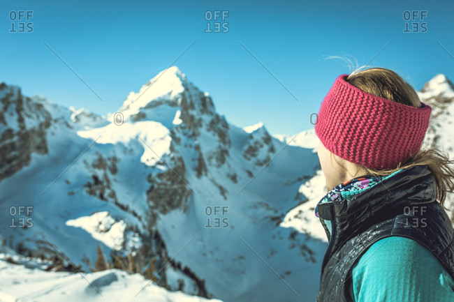 Side view of woman standing against snowcapped mountains