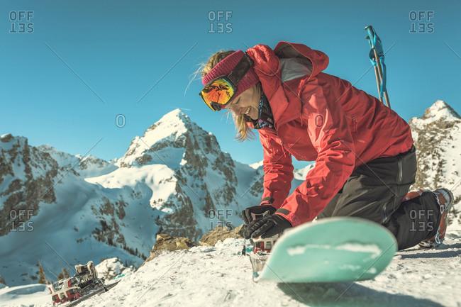 Woman fixing ski against snowcapped mountains