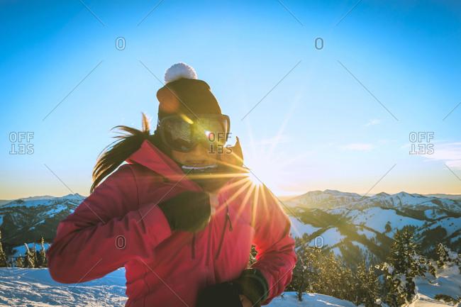 Woman wearing ski-wear against blue sky