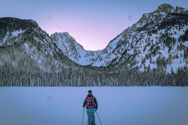 Rear view of woman with ski poles standing against snow covered mountains