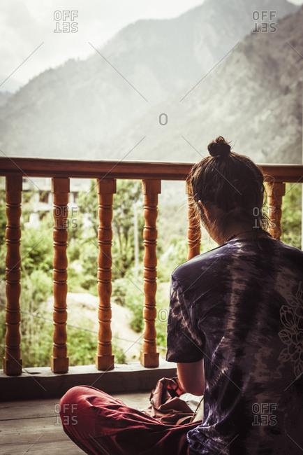 Rear view of woman sitting in balcony