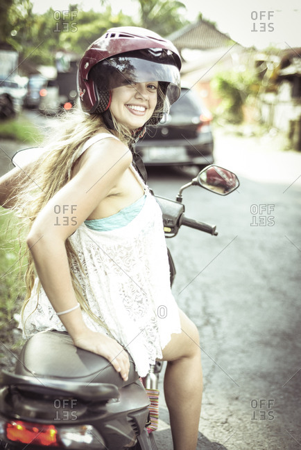 Portrait of smiling woman sitting on motor scooter