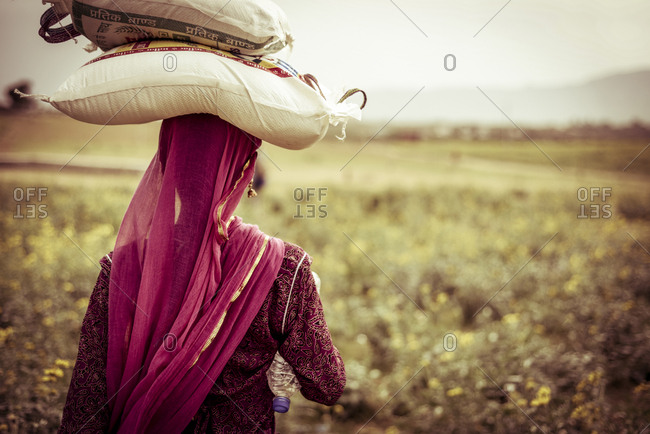 Rear view of woman carrying bags on head at farm
