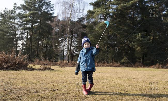 Full length boy with golf stick walking on field
