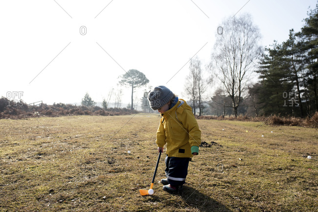 Girl playing miniature golf on field against sky