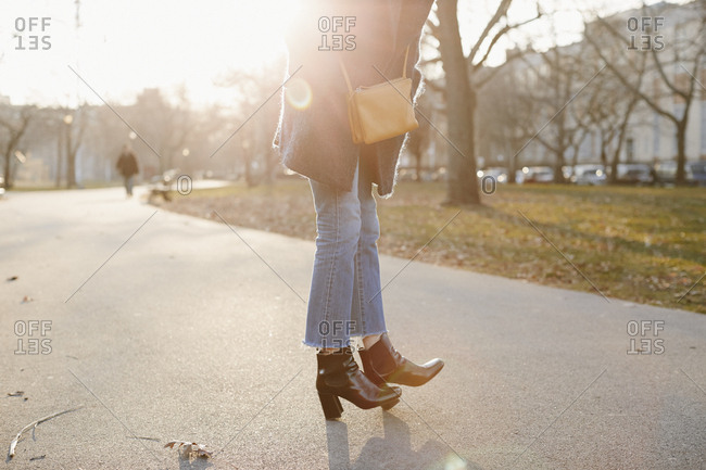 Low section of woman standing on footpath during sunny day