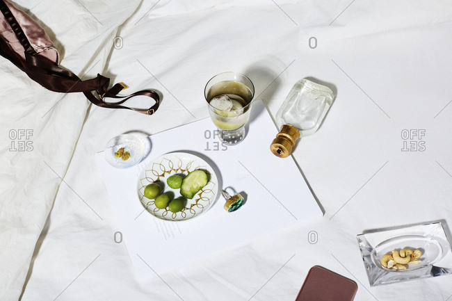 High angle view of food and drink with personal accessories on bed