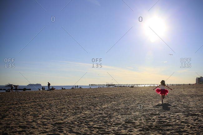 Rear view of girl walking on sand at beach against sky
