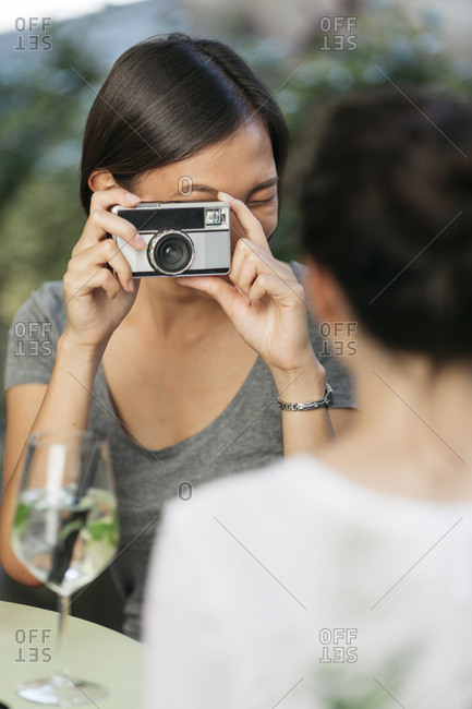 Young woman taking picture of her friend with camera at sidewalk cafe