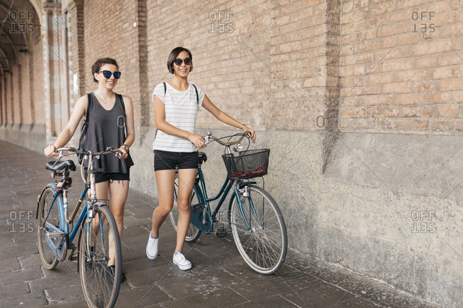 Two young women pushing their bikes