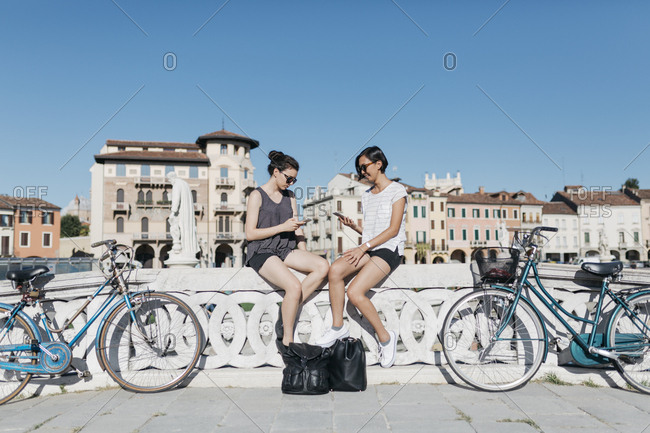 Italy- Padua- two young tourists sitting on railing looking at cell phones