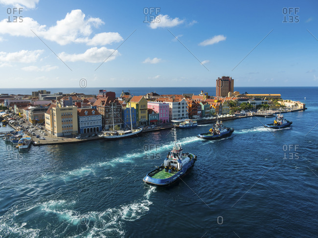 Punda, Willemstad, Curacao - March 3, 2016:  Tugboats and colorful houses at waterfront promenade