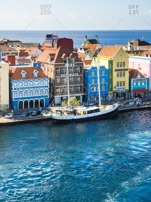 Punda, Willemstad, Curacao - March 3, 2016:  Schooner and colorful houses at waterfront promenade