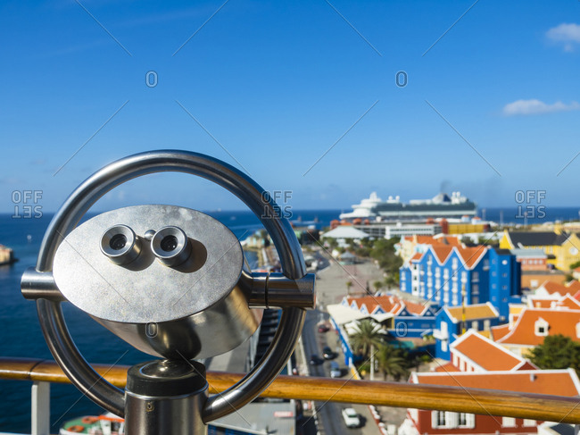 Curacao- Willemstad- Punda- coin-operated binocular and colorful houses at waterfront promenade