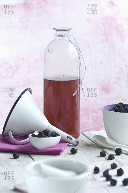 Glass bottle of homemade sloe sirup- funnel and fruits