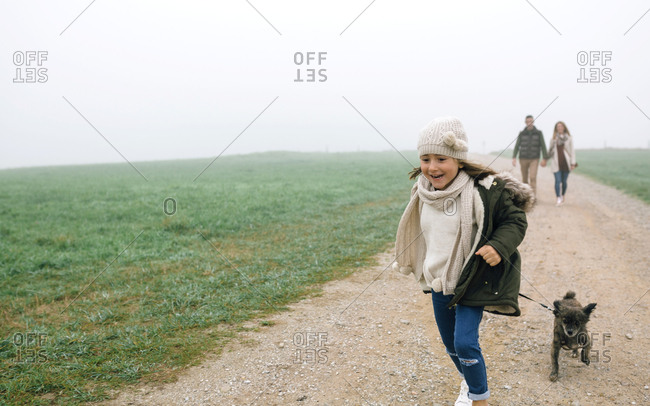 Happy girl running with her dog while her parents walking in the background on a foggy day in winter