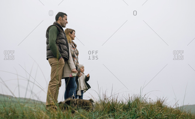 Family with dog standing on a meadow on a foggy winter day