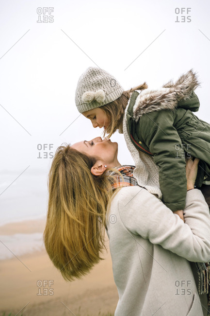 Woman lifting up and kissing daughter on the beach in winter