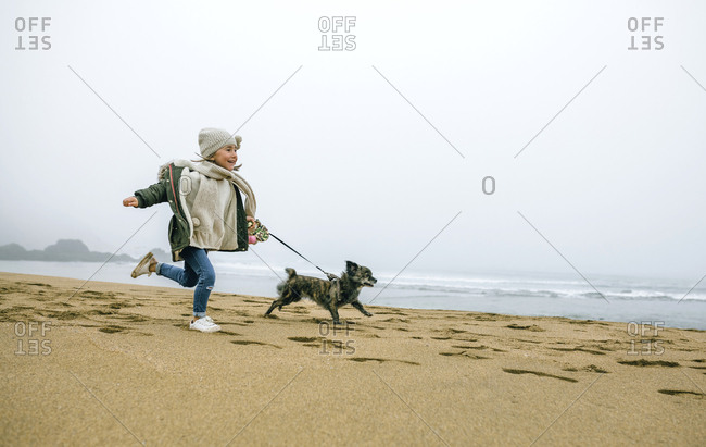 Happy girl running with dog on the beach on a foggy winter day