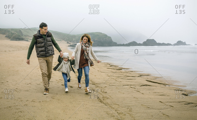 Happy family with daughter walking on the beach in winter