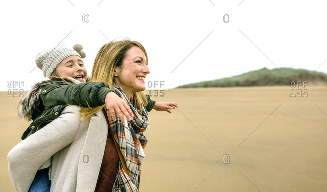 Happy woman carrying daughter piggyback on the beach in winter