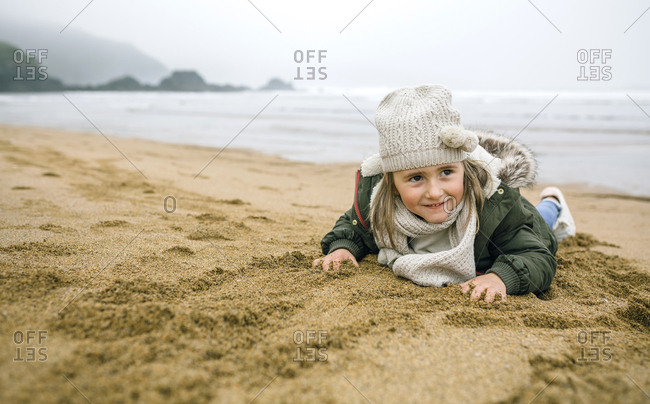 Happy girl lying in sand on the beach in winter