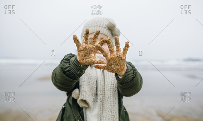 Girl showing her sandy hands on the beach in winter