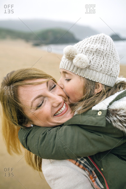 Girl kissing happy mother on the beach in winter
