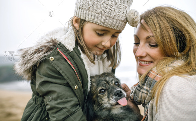 Mother and daughter stroking their dog on the beach in winter