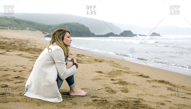 Lonely woman sitting on the beach in winter