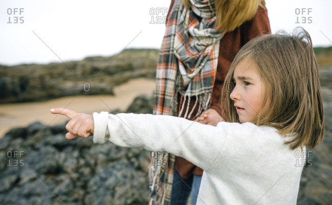 Girl with mother pointing her finger on the beach in winter