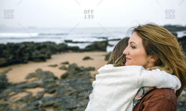 Mother holding daughter on the beach in winter
