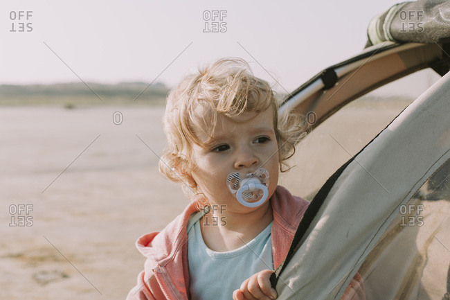 Netherlands- Schiermonnikoog- little girl looking out of bicycle trailer on the beach
