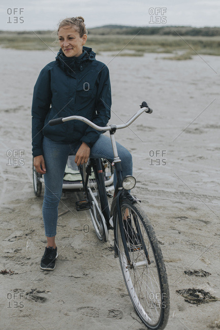 Netherlands- Schiermonnikoog- woman with bicycle and trailer on the beach