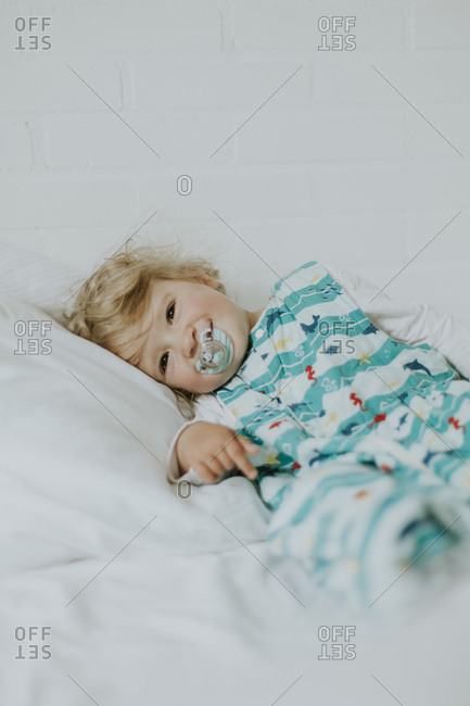Little girl with pacifier lying in bed
