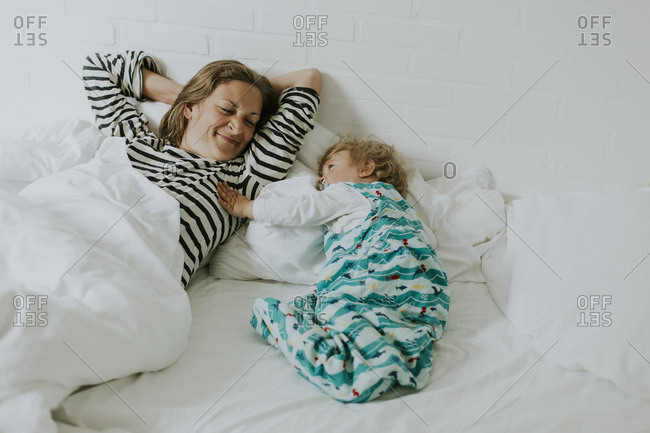 Mother and little daughter in bed