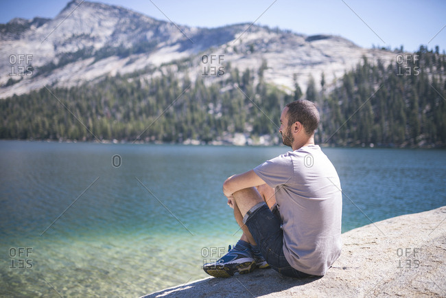 USA- California- Yosemite National Park- man sitting at mountain lake