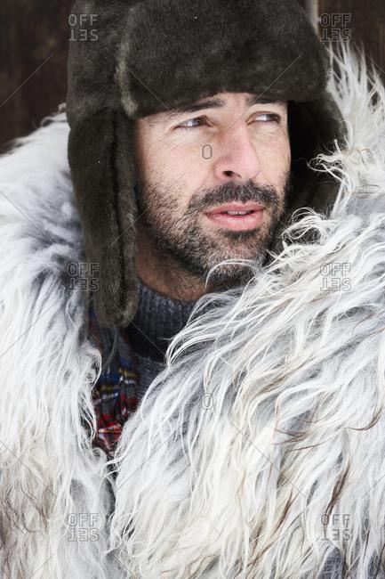 Portrait of man wearing fur cap in winter