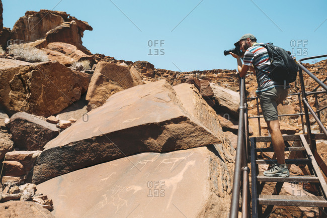 Namibia- Damaraland- Twyfelfontein- Man taking pictures of petroglyphs