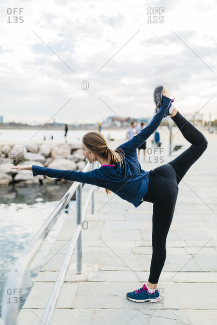 Young woman doing yoga poses at the the beach